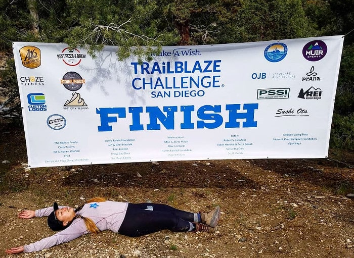 Liz at the finish banner for the Trailblaze Challenge!